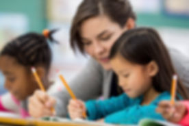 Teacher helping a little girl with her school work