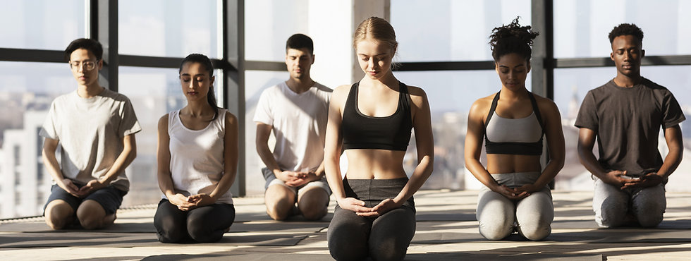 Group meditating peacefully after a yoga class in filtered sunlight