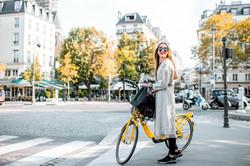 woman walking next to her bike on a sidewalk