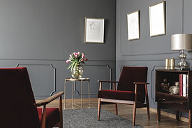 Red chair in front of dark grey walls next to gold coffee table and a vase of pink flowers