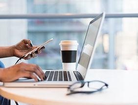 Social media trainer on laptop in cafe