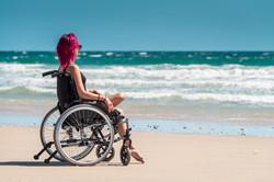 Donna in sedia a rotelle in spiaggia