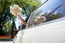 Bruid zwaaien bloemen in Limo