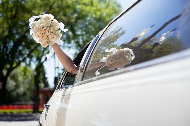 Bride Waving Flowers in Limo