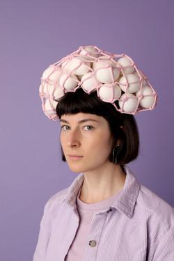 Mulher com cabelo chanel com um saco de ovos em cima da cabeça.
