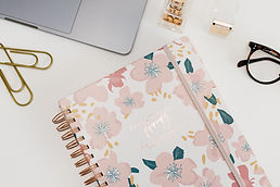 Cute Planner with a laptop and glasses on the top of a desk.