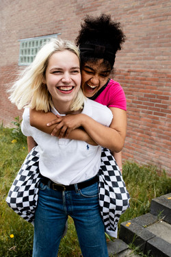 A young interracial couple laughs while giving a piggy back ride