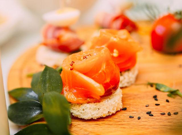 Un roulé de saumon sur un blinis avec des petites baie dessus et de la verdure à côté