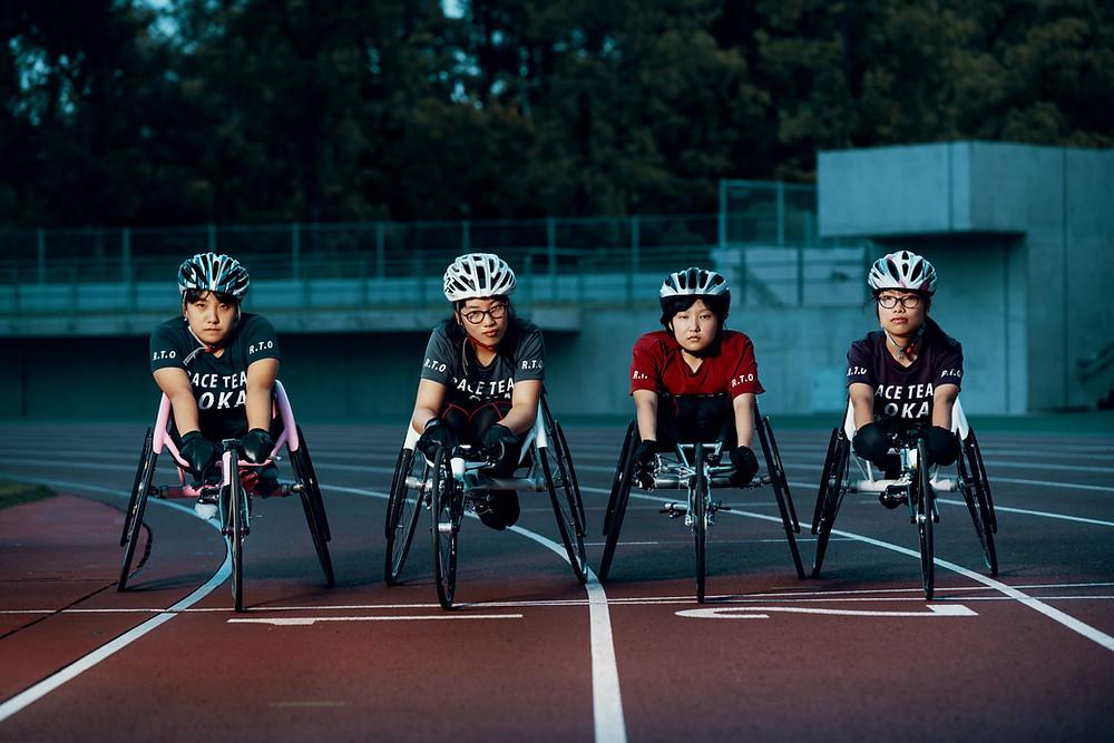 Quatro mulheres asiáticas usam capacete de ciclismo e estão em cadeiras de rodas em uma pista de atletismo.