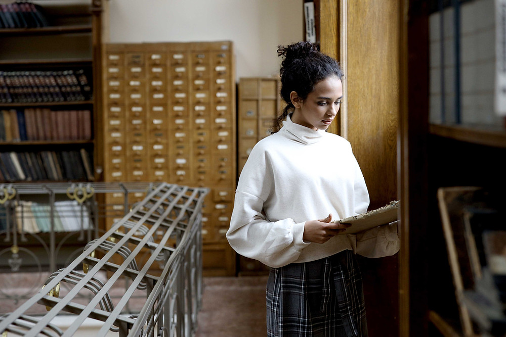 woman in library looking through a rare book