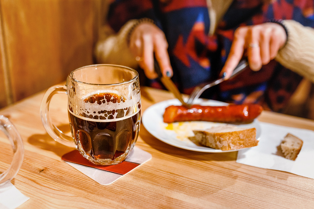 half drunk beer, eating sausage on a plate