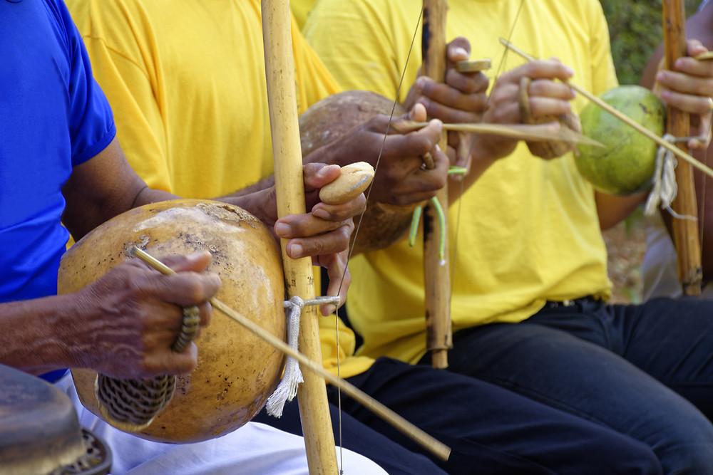 3 homens tocando o berimbau em uma roda de capoeira