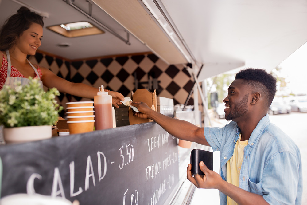 Black man paying female worker for food at a food truck.