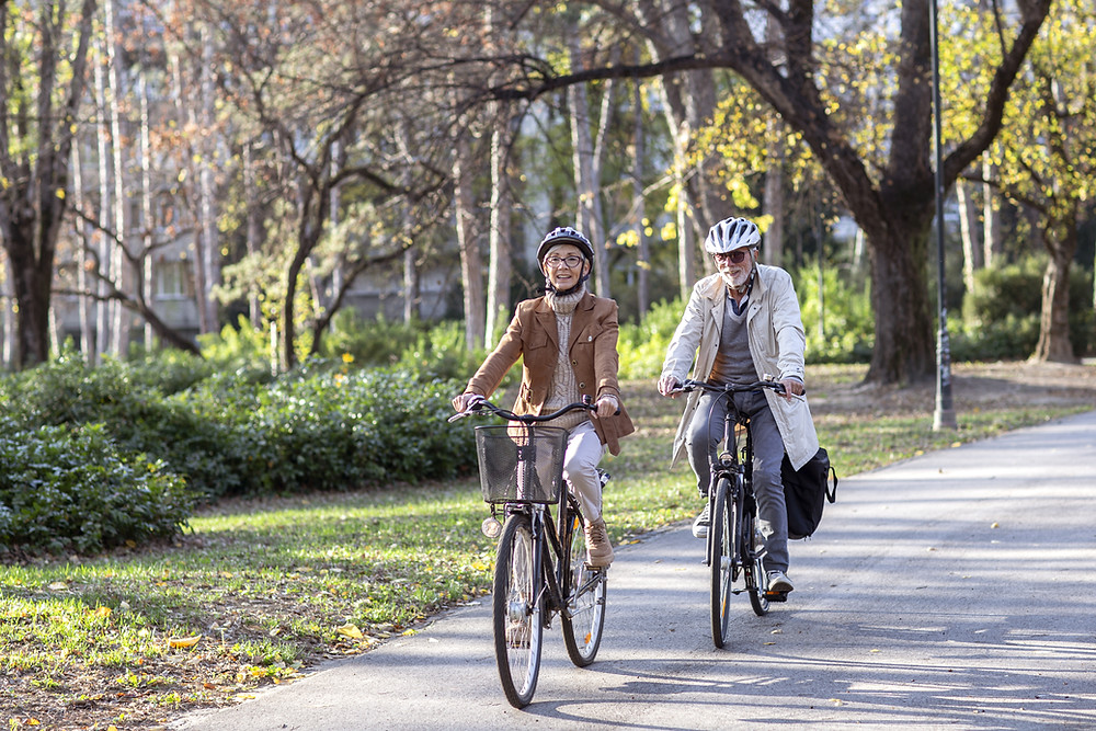 two elderly people cycling as part of a healthy lifestyle