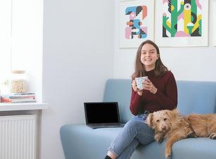 女性と犬がソファに座っている