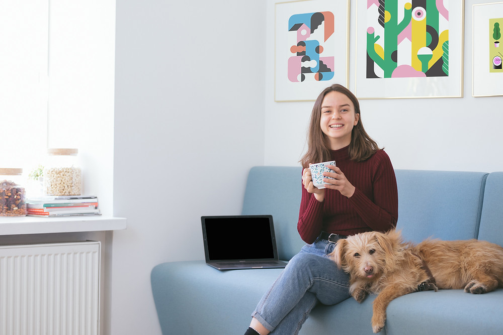 Girl holding a mug of tea. Girl is sitting on a lounge with a dog next to her on the lounge. There is a laptop on the lounge to the girl's right.