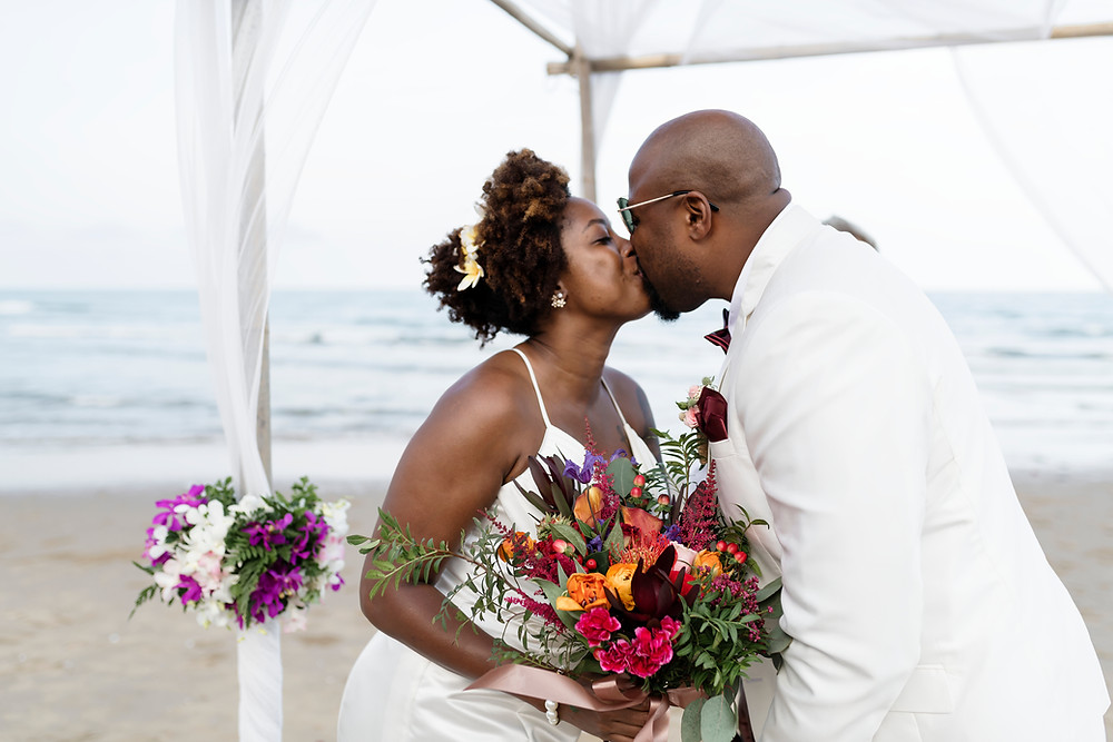 A bride and groom kissing passionately at their small beach wedding in Denmark