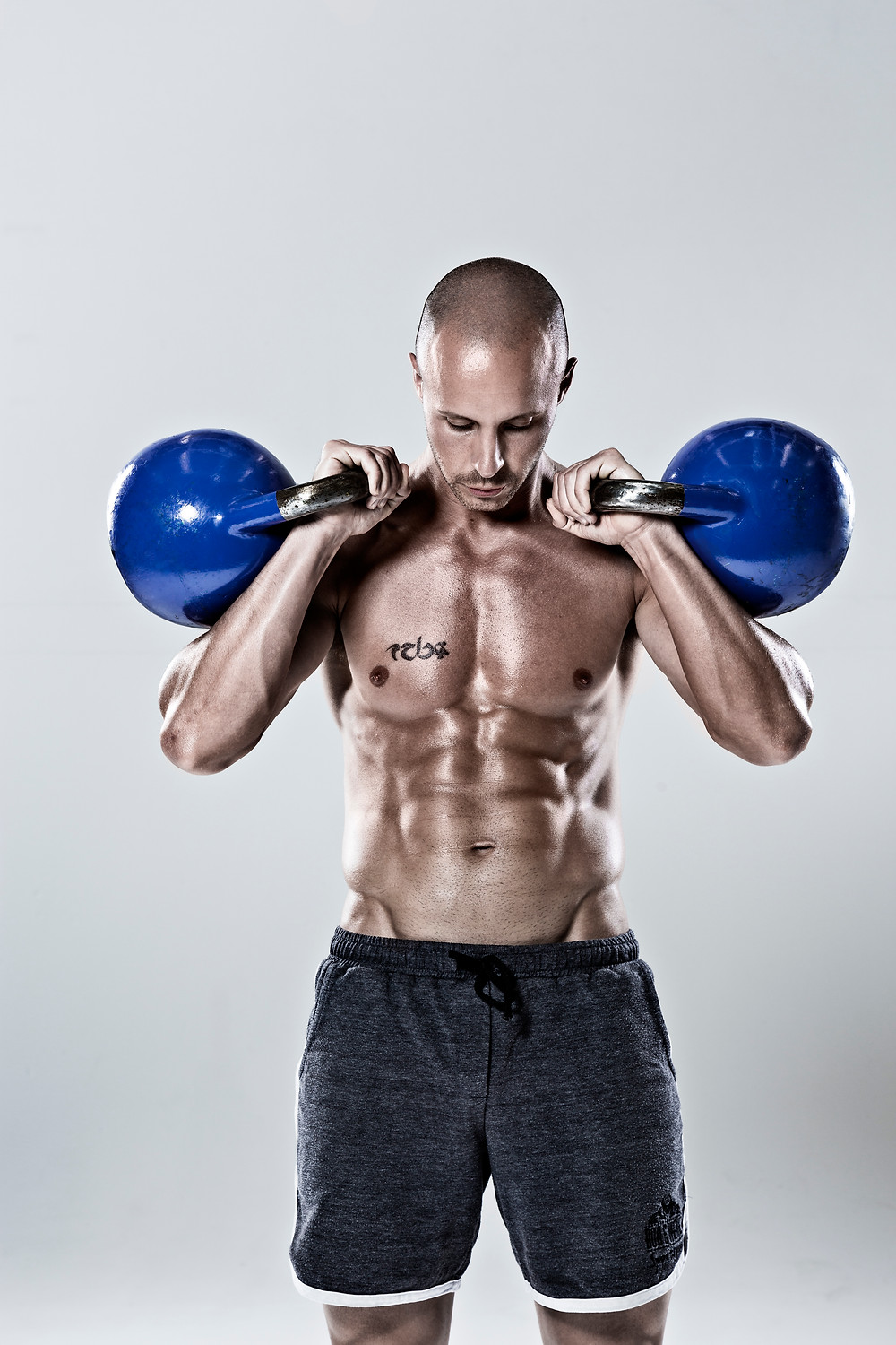 a man standing with two competition kettlebells