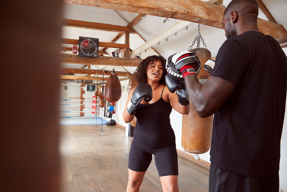 Two people practicing boxing training. One is holding a pair of focus pads and the other person is boxing the pads. They are in a boxing gym surrounded by heavy punch bags, uppercut bags and speed bags.