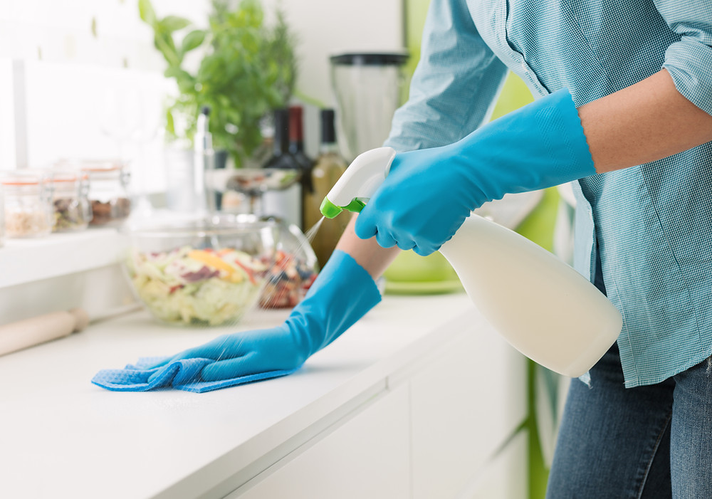Woman cleaning kitchen counter with a spray bottle.