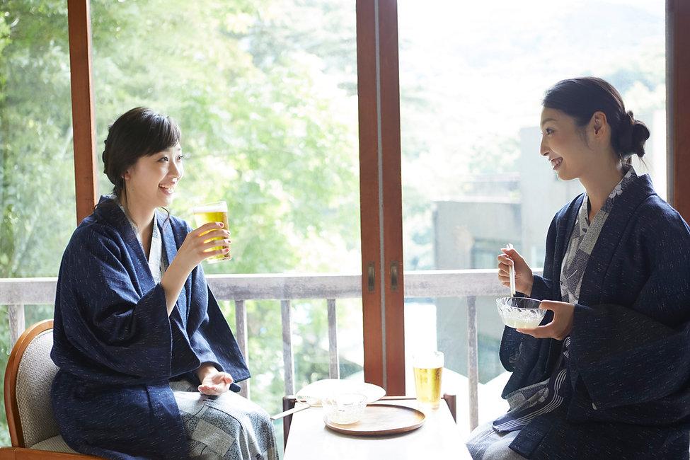旅館でビールを飲む女性