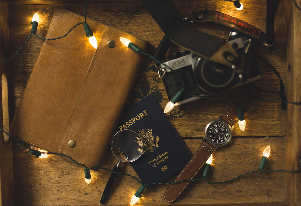 Passport, camera & travel accessories on a table with string of white lights.