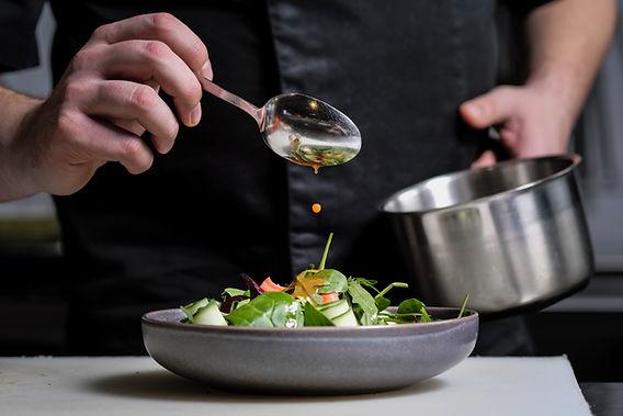 Un hombre preparando una ensalada