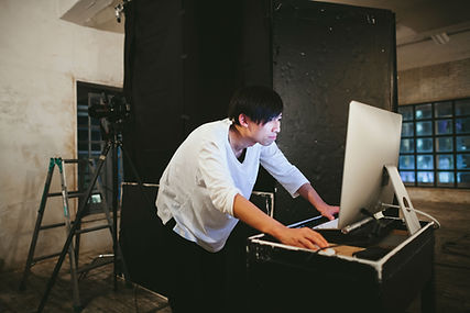 A middle aged asian man in a white sweater is standing and leaning forward while looking at a large computer screen, his right hand is no the mouse. His back is hunched.