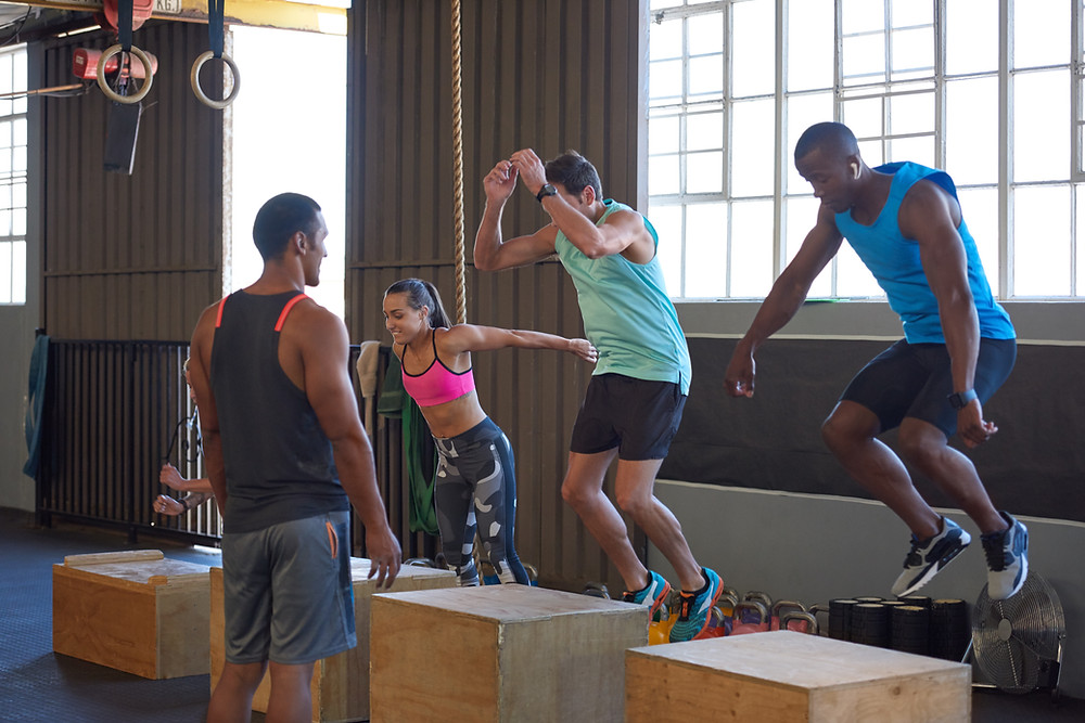 people in a gym performing plyometric exercises