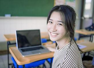 机に座って笑顔の学生