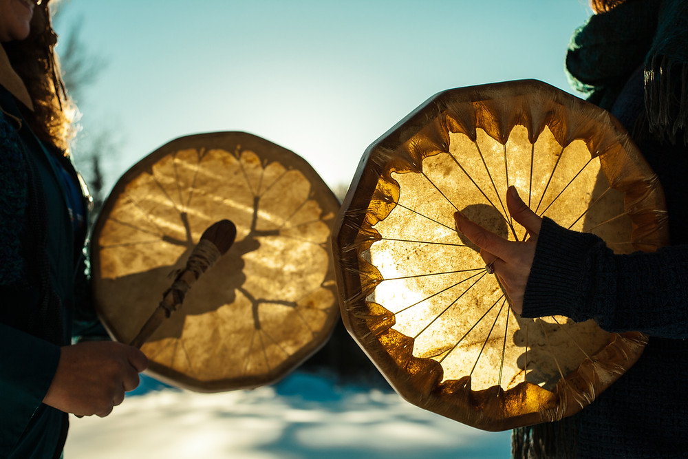 Two people holding indigenous drums in a traditional ceremony.