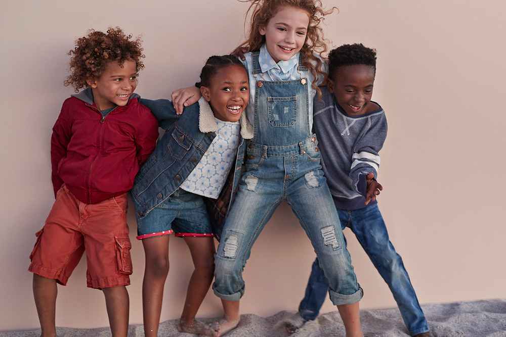 4 child models playing laughing in denim outfits