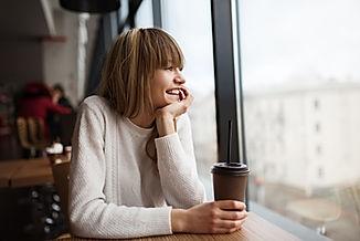 Imagem de uma moça sentanda em uma mesa de café rindo e tomando um café olhando pela janela Imagem de uma loja do Mcdonalds inserida na página de vendas do curso Marca a Alma de todo negócio, sobre Branding ou Gestão de Marcas