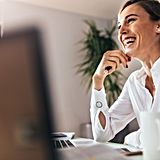 Eine Frau sitzt vor dem Computer und übt ein Bewerbungsgespräch mit einem Lehrer