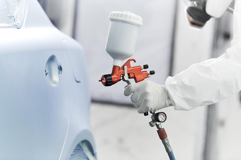 Mechanic spraying a car, vehicle spray paint body repair work
