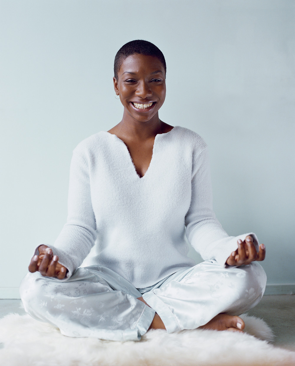 Woman smiling in mediation position.