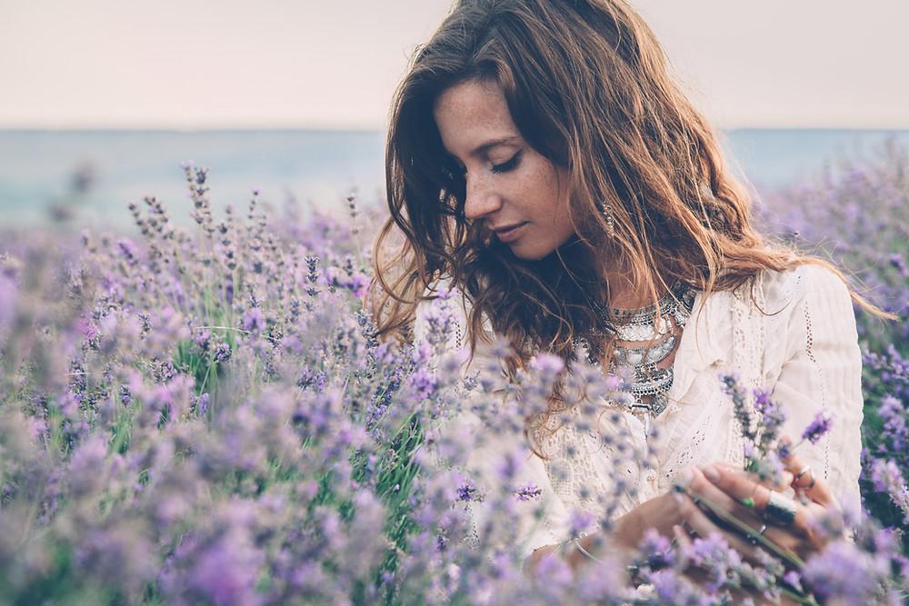 Jeune femme dans un champ de lavande, semble apprécier le moment de cueillette et de senteurse