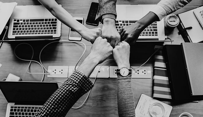 colleagues fist bumping above a desk