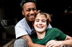 A young interracial couple holding each other and smiling