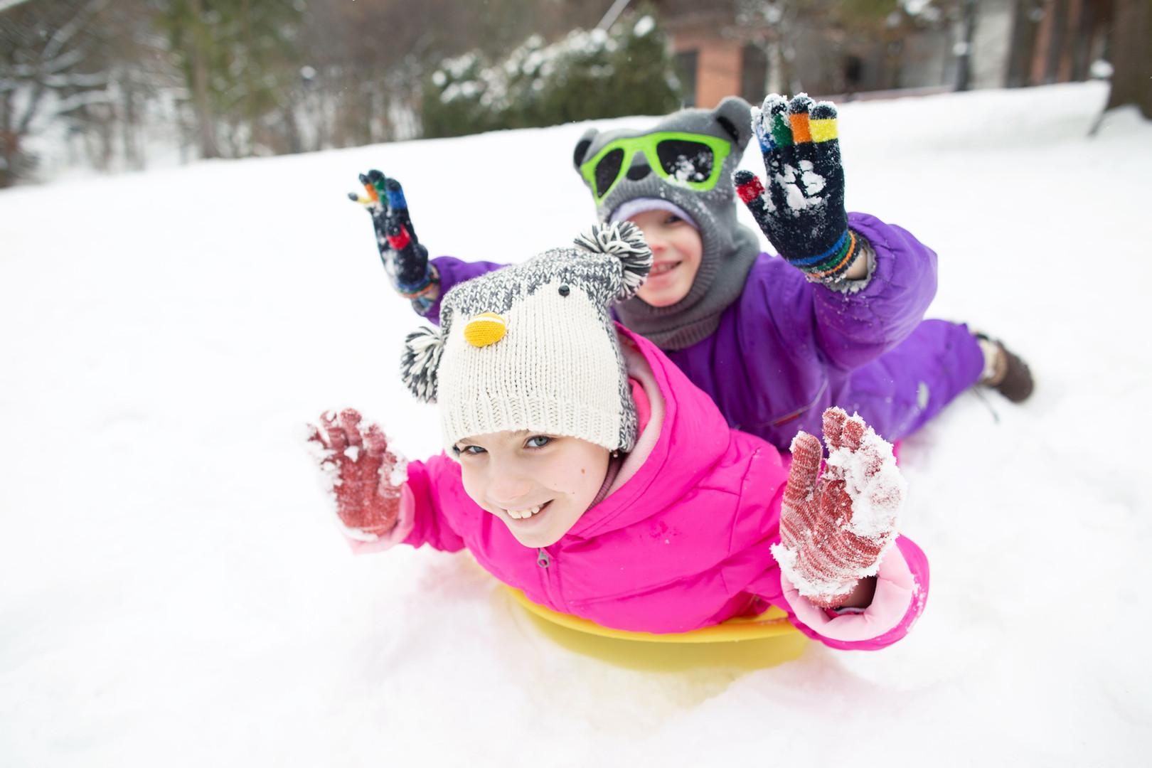 Glückliche Kinder im Schnee rodeln