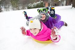 Niños felices en trineo en la nieve