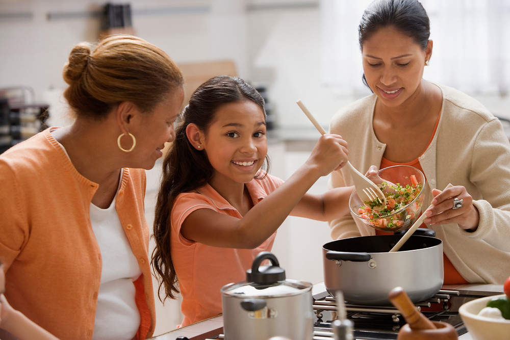 mother, daughter and granddaughter cooking together