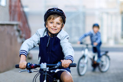 group of kids riding their bicycles with helmets