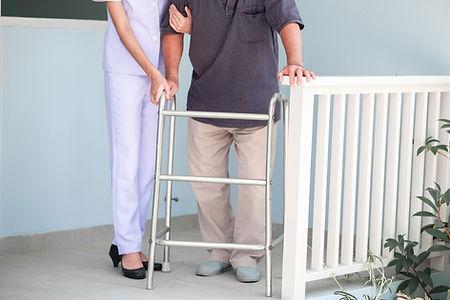 歩行器で歩く男性