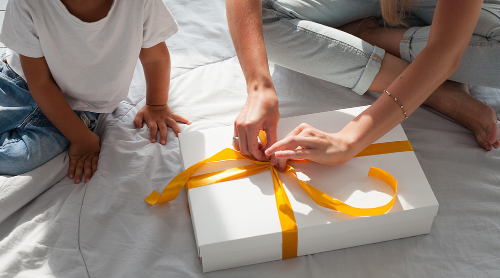 Mom and her child opening a present on the bed