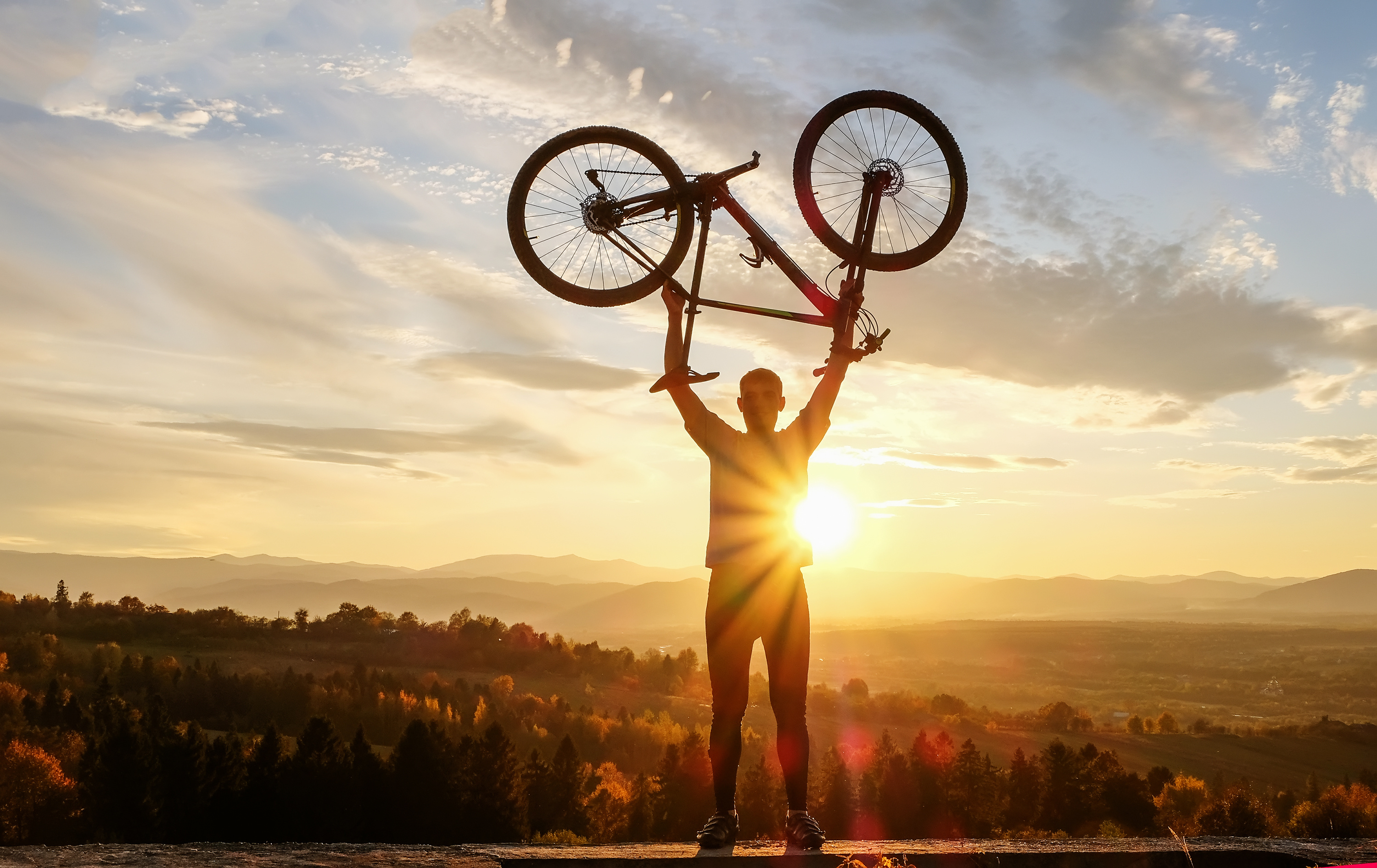 Man holding a bicycle above his head in front of a sunset