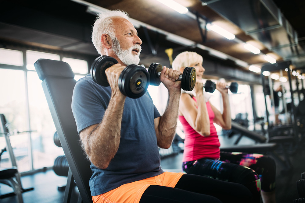 Older man and women in the gym, fitness after 50