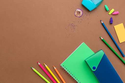 Colored pencils, erasers, noteook, pencil case, and pencil shavings.