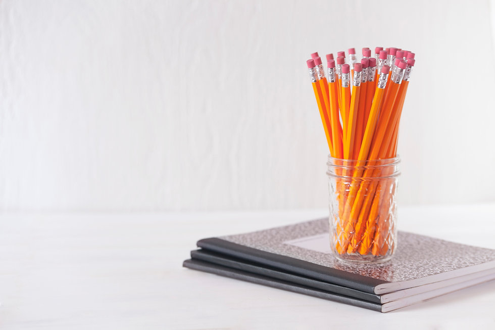A clear glass jar filled with unsharpened No. 2 pencils sitting atop a stack of 3 B&W notebooks.