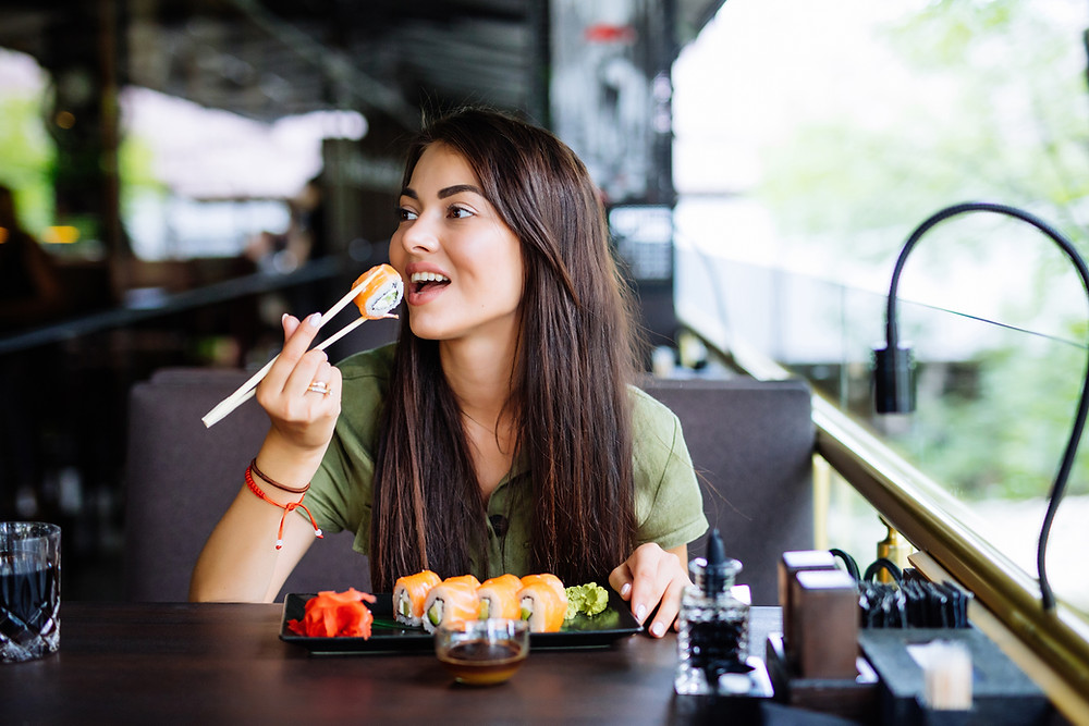 Girl eating sushi in a restaurant
